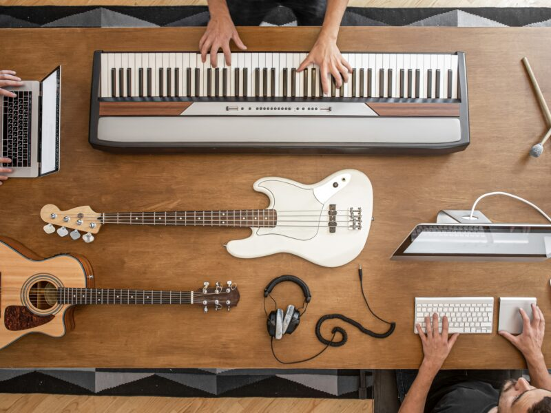 On a wooden table there are musical keys, acoustic guitar, bass guitar, sound mixer, headphones, computer and drum sticks.